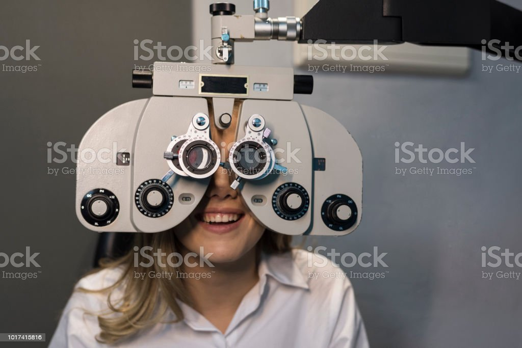 Woman ready for eye test with phoropter and calibrating glasses stock photo