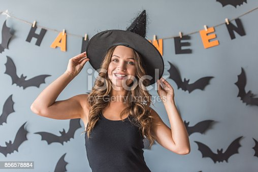 Beautiful young woman in witch hat is looking at camera and smiling, on background decorated for Halloween
