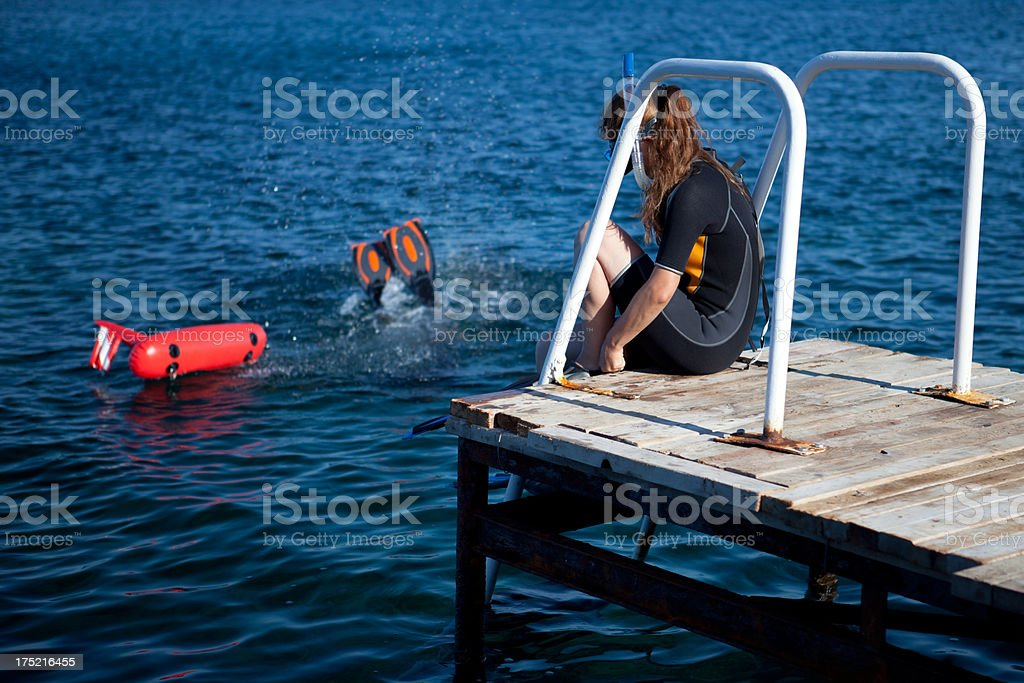 Woman ready to dive, man is into the water royalty-free stock photo