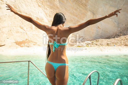 Rear view of woman ready to jump into water, from an yacht.