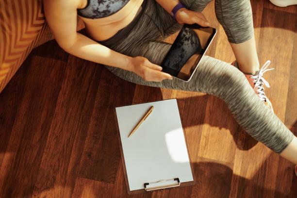 kvinna redo att göra anteckningar medan du tittar på träningsprogram - calendar workout bildbanksfoton och bilder
