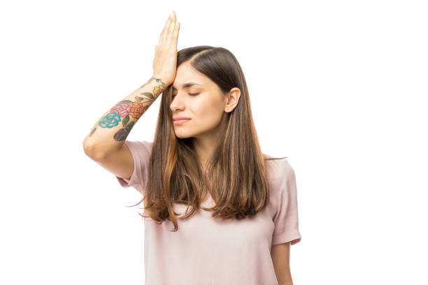 Woman Realizing Mistake And Keeping Hand On Head Woman realizing mistake and keeping hand on head over white background guilty stock pictures, royalty-free photos & images