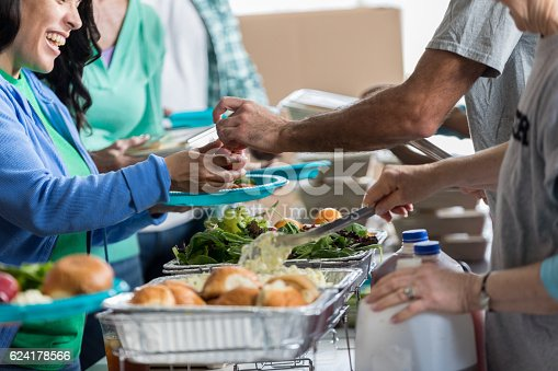 istock Woman receives a healthy meal at soup kitchen 624178566