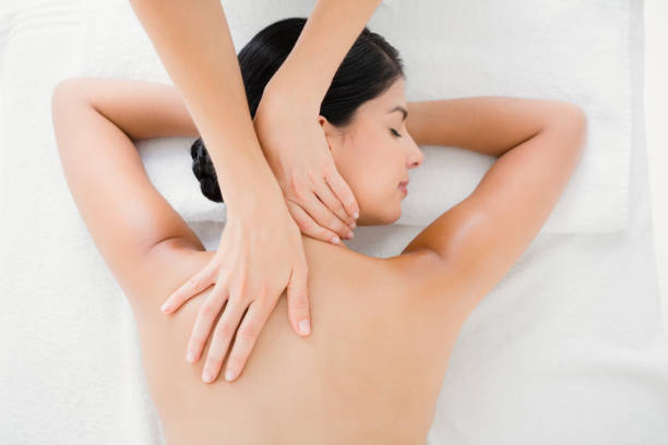 woman receiving a back massage - massaggio foto e immagini stock