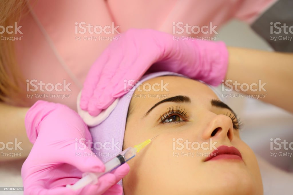 Woman receiving a botox injection in the eye zone lying in bathrobe on the medical couch stock photo