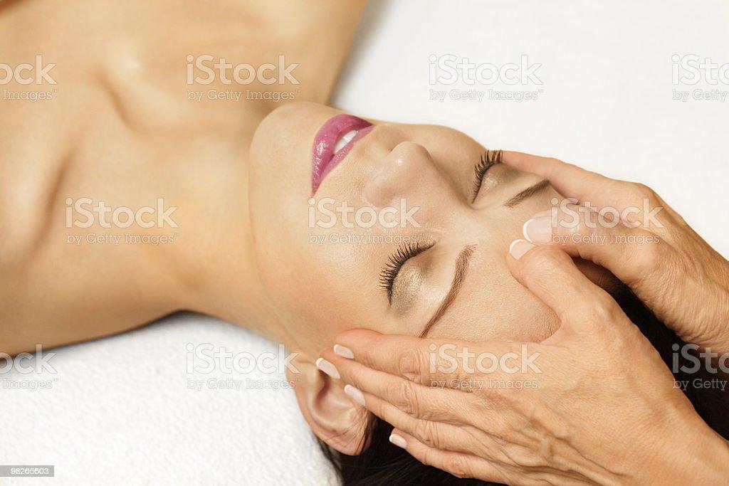A woman receiving a facial massage stock photo