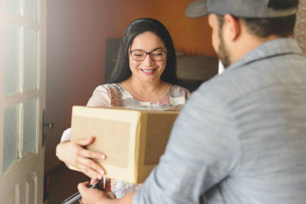 Woman receiving a package at home from delivery man stock photo