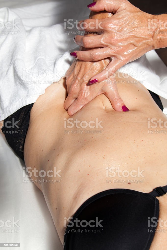 Woman receiving a professional masagge and lymphatic drainage various techniques stock photo