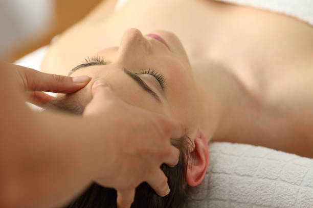 Woman receiving a relaxing facial massage Closeup of a woman receiving a relaxing facial massage in a spa human skull stock pictures, royalty-free photos & images