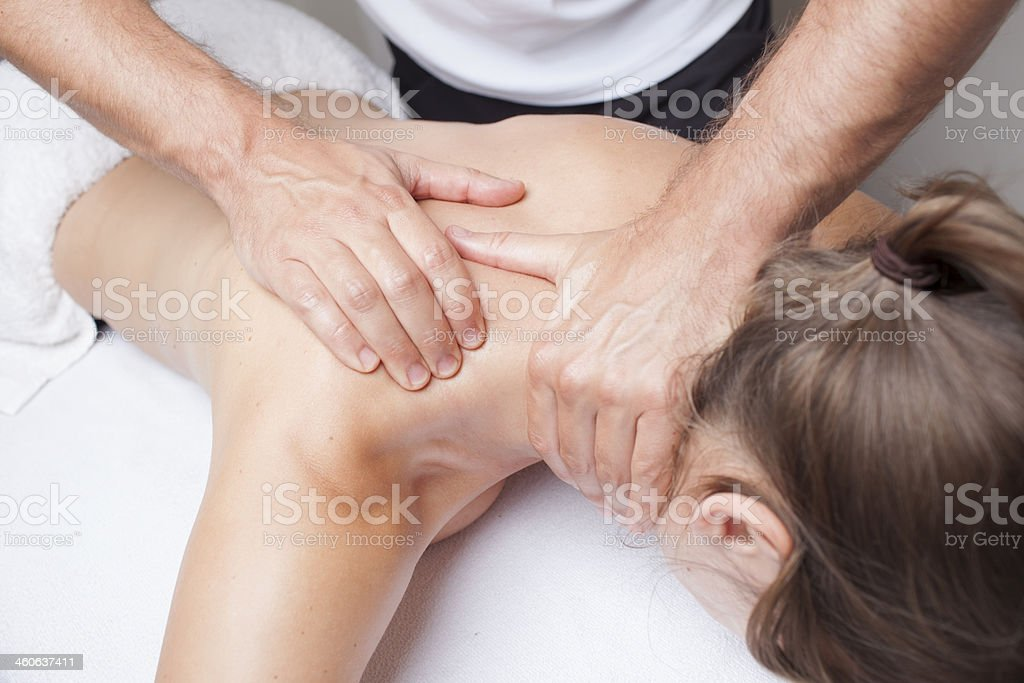 Woman receiving a shoulder massage from a male stock photo