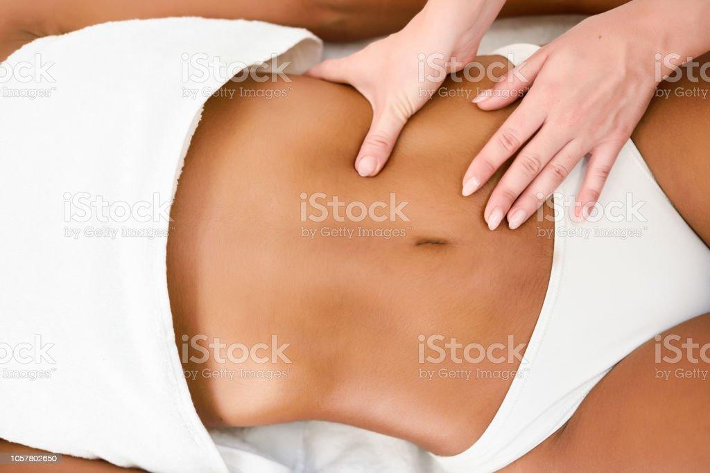 Woman receiving abdomen massage in spa wellness center. stock photo