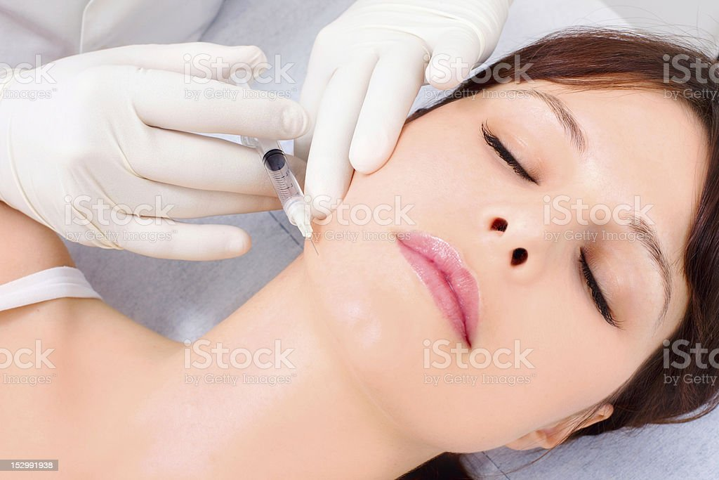 woman receiving an injection of botox from a doctor royalty-free stock photo