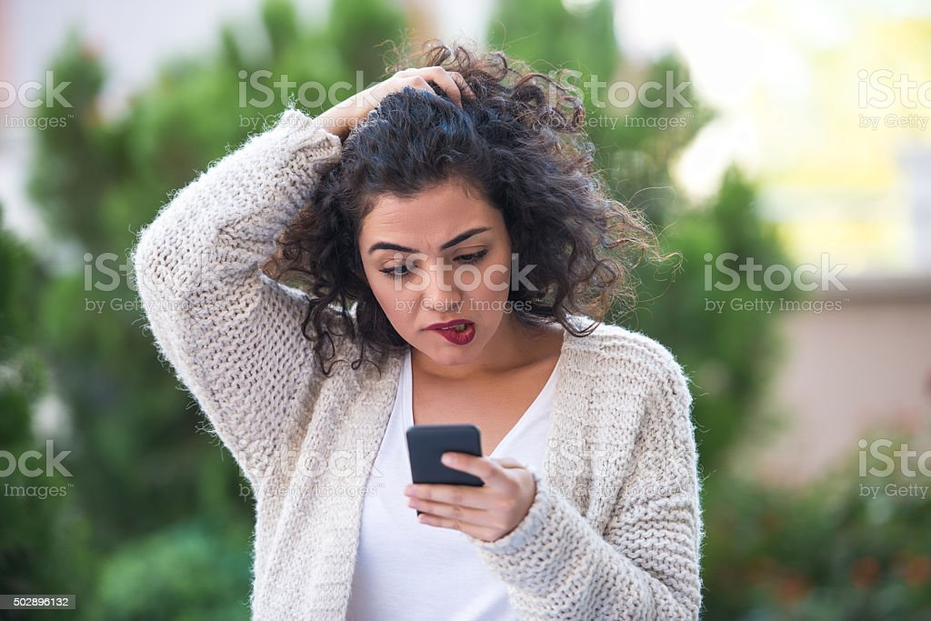 Woman receiving bad news on smartphone stock photo