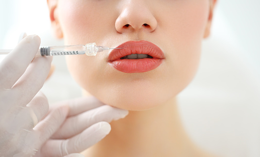Closeup of crop anonymous female patient getting filler injection in lips in cosmetology clinic