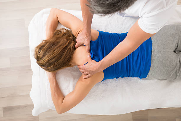 woman receiving body massage - massage therapist stock pictures, royalty-free photos & images