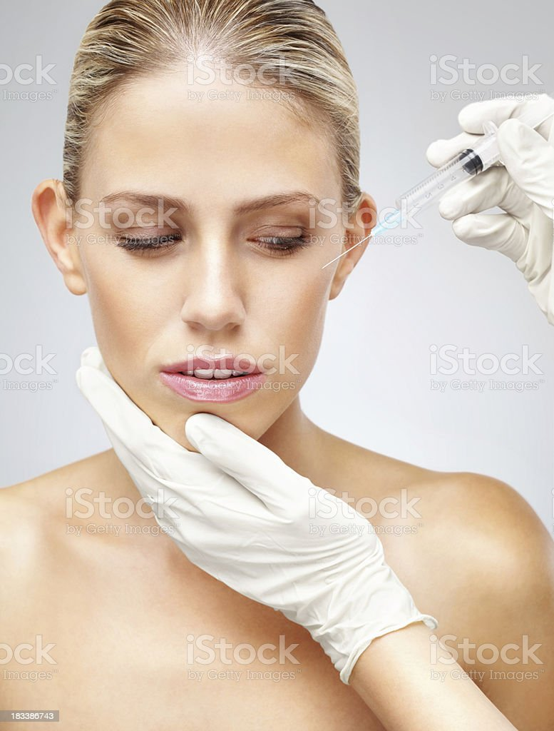 Woman receiving Botox injection against grey background royalty-free stock photo