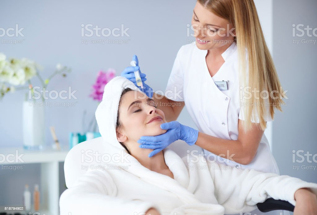 Woman receiving botox injection in clinic - foto stock
