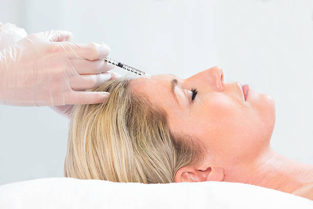 femme recevoir injection de botox - injection de toxine botulique photos et images de collection