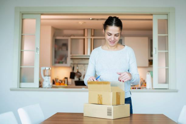 Woman receiving delivery at home stock photo