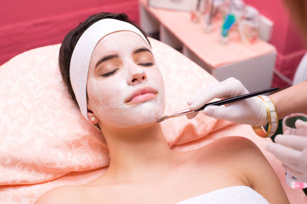 woman receiving facial mask treatment - peeling off stock photos and pictures