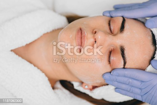 istock woman receiving facial treatment at beauty salon. Exfoliation 1137092300