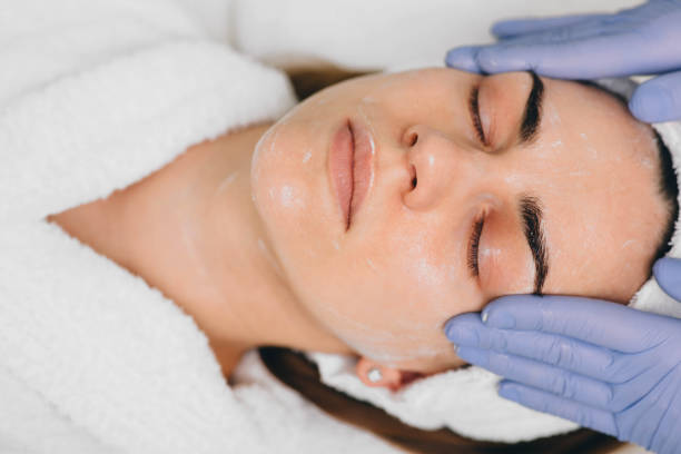 woman receiving facial treatment at beauty salon. Exfoliation beautiful woman having her face pampered at beauty salon by her beautician skin stock pictures, royalty-free photos & images