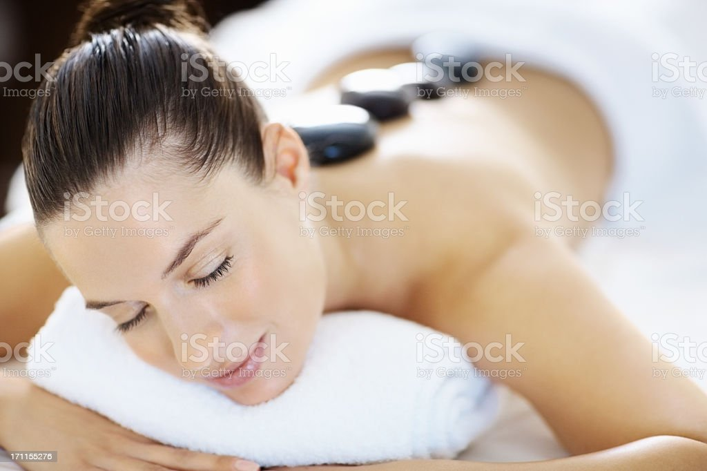 A woman receiving hot stone therapy stock photo