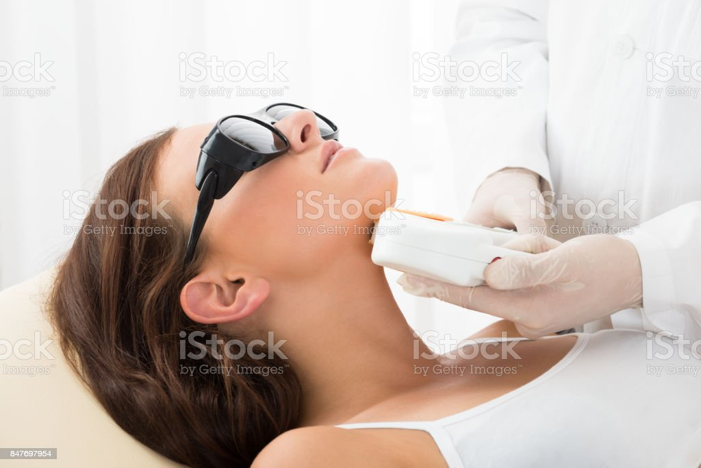 Woman Receiving Laser Hair Removal On Neck stock photo