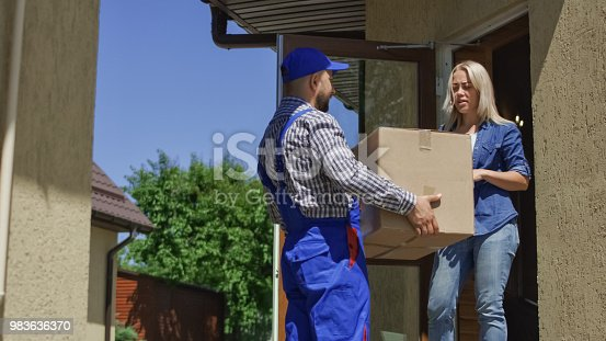 istock Woman receiving mail box with courier 983636370