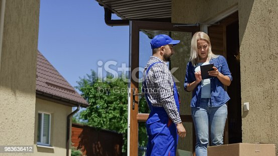 istock Woman receiving mail box with courier 983636412
