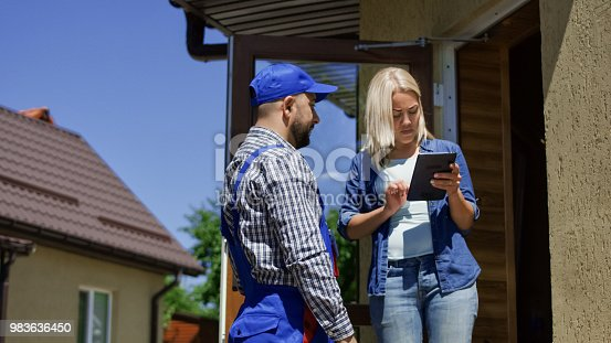 istock Woman receiving mail box with courier 983636450