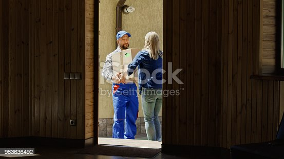 istock Woman receiving mail box with courier 983636492