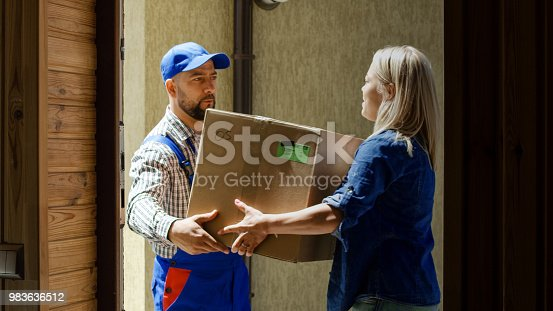 istock Woman receiving mail box with courier 983636512