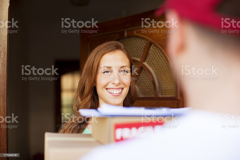 Woman receiving multiple packages at front door royalty-free stock photo