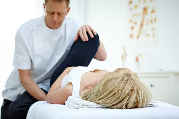 Woman receiving osteopathic therapy on her leg stock photo