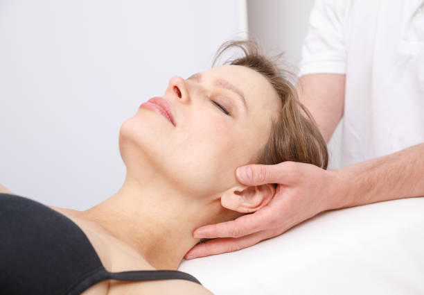 Woman receiving osteopathic treatment of her neck Young woman's neck being manipulated by osteopathic or chiropractic manual therapist human skull stock pictures, royalty-free photos & images