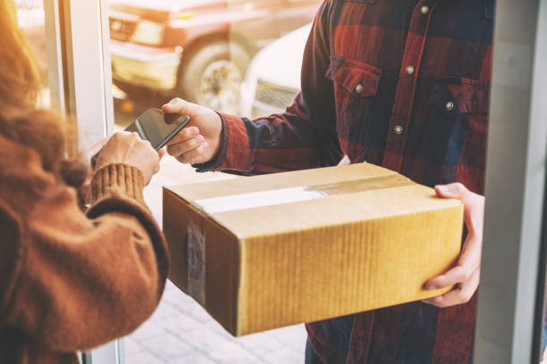 Frau erhält Paketkasten und Unterschrift Namen auf dem Telefon von Liefermann – Foto