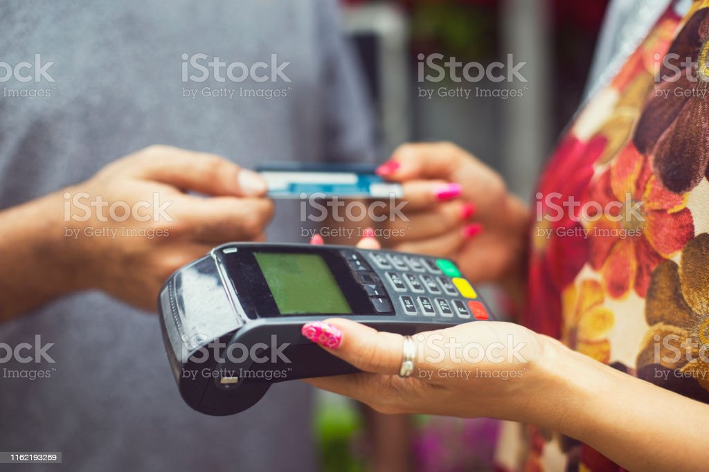 Woman using digital device to receive payment through credit card