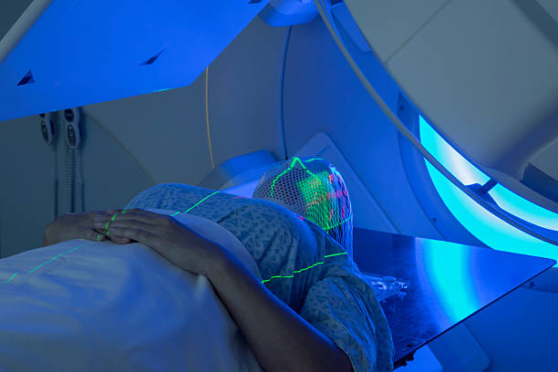 woman receiving radiation therapy treatments for head & neckcancer - strahlung stock-fotos und bilder