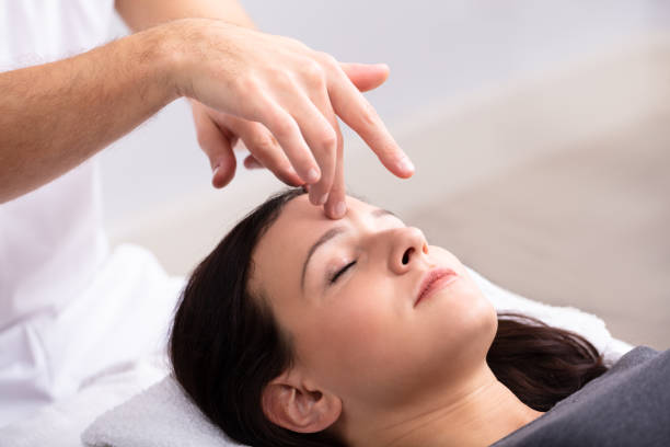 femme recevant un traitement de reiki - réflexologie photos et images de collection