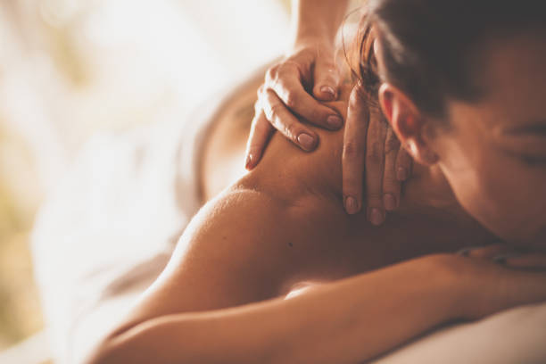 woman receiving shoulder massage at spa - massaggio foto e immagini stock