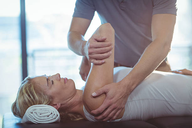 woman receiving shoulder therapy from physiotherapist - handmuskeln stock-fotos und bilder