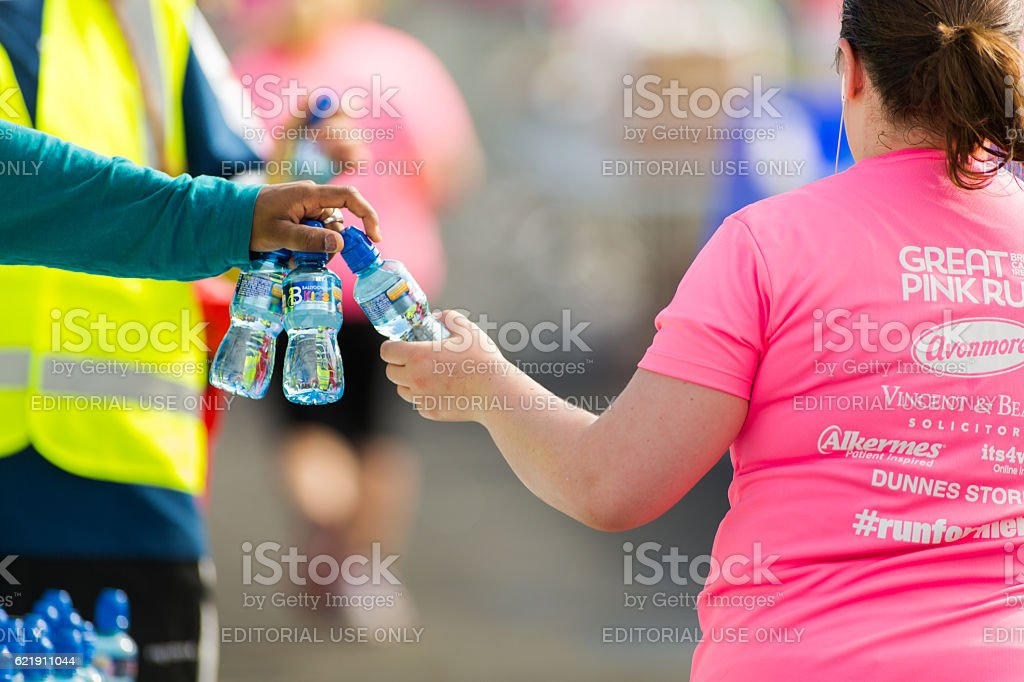 Woman receiving water during marathon stock photo