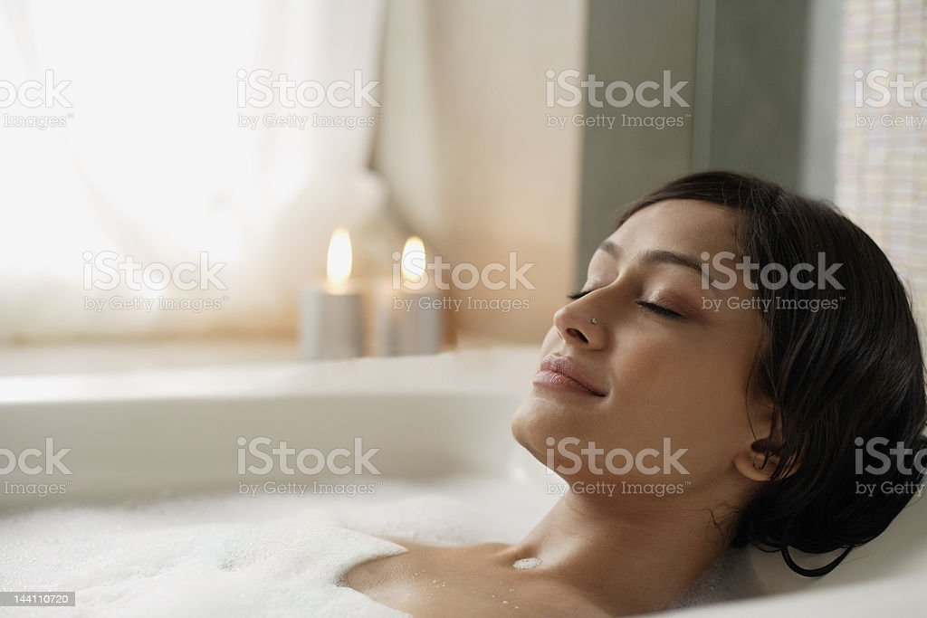 Woman reclining in bathtub stock photo
