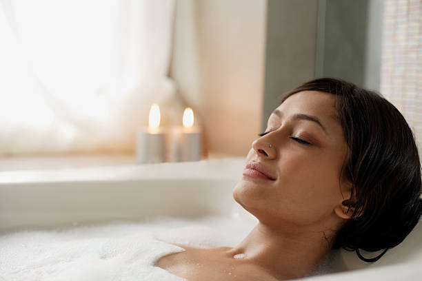 Woman reclining in bathtub  bathtub stock pictures, royalty-free photos & images