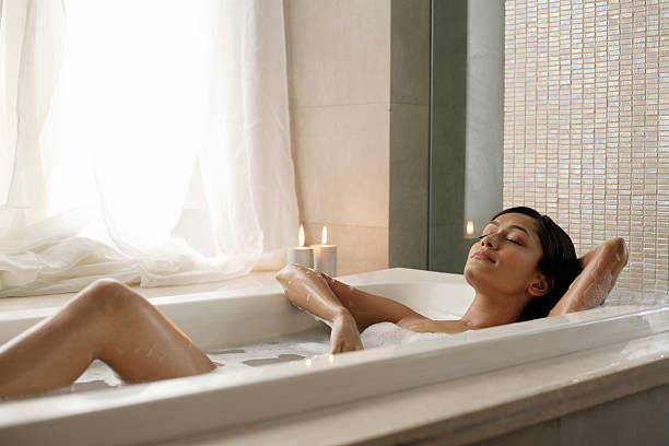 Woman reclining in bathtub Woman reclining in bathtub bathtub stock pictures, royalty-free photos & images