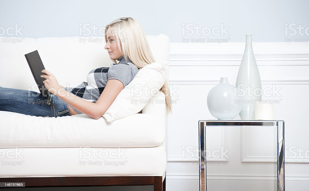 Woman Reclining on Couch With a Book royalty-free stock photo