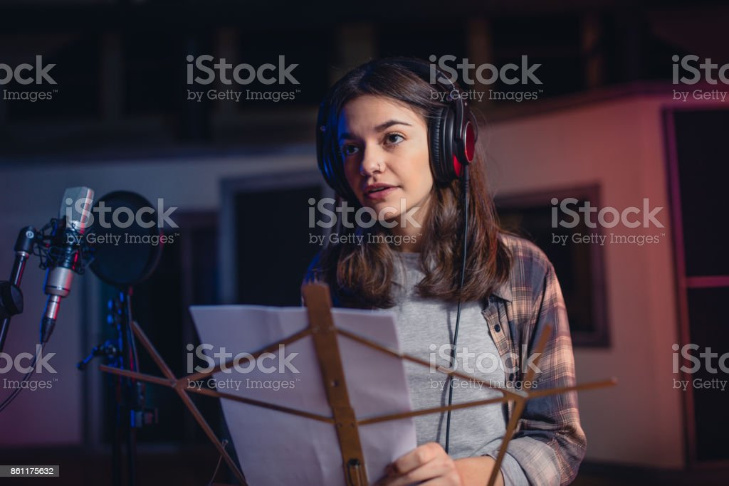 Woman recording a song in music studio stock photo