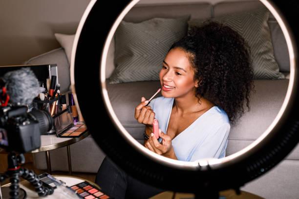frau aufzeichnung make-up-tutorial mit dslr und ringlicht - gesicht make up anleitungen stock-fotos und bilder