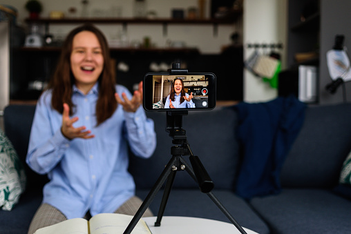 Smiling Woman in shirt Recording video at home for her video blog. Using smartphone